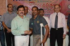 Administrator Korangi giving Rs. 10,000 to Farhan Saeed