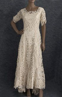 Battenburg silk lace wedding dress, c.1905. Made from hand-assembled     silk Battenburg lace, the long princess-line shaping fits smoothly through the upper torso, flares     below the hipline, and ends in a graceful back train. The mellow champagne hue glows with romantic conjugal love