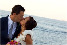 Newlywed kiss. Summer Malta wedding. Maltese wedding day. Seaside weddings. Weddings abroad. Bride style ivory satin fishtail wedding dress with one rouched shoulder strap detail. Button up corset back. Bridal hair, loosely twisted chignon. Medium length dark hair. Natural wedding day makeup. Bride trend fashion. Groom trend style dark blue suit light blue shirt. Natural wedding photography