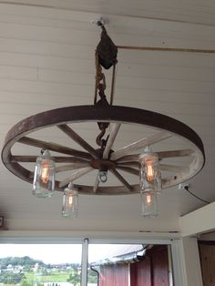Lamp made of an old wheel from a wagon used on our farm in the old days. Pulley and old jars found on the farm. Lamp designed by me and set together by my husband♥