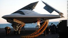 The X-47B is loaded onto an aircraft elevator in the Atlantic Ocean off the coast of Virginia.