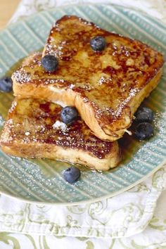 Sunday Morning Blueberry Bourbon French Toast: 8 pieces Texas Toast or other thick-cut bread 1 ½ cups whole milk 3 large eggs ¼ cup bourbon 1 tsp. vanilla extract 2 tsp. ground cinnamon 2 tbs. butter Handful of blueberries Powdered sugar Maple syrup