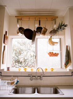 pot rack. towel hung right at sink (to keep hubs from dripping all over the floor in search of a towel). fruit basket.