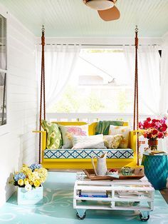 Makeover a covered porch to fit the season by copying this home's summer porch decorating ideas. Bring out colorful pillows and a plush swing cushion for cozy seating. Vibrant flowers and summer patio plants bring nature into the mix. A pallet coffee table on casters allows for entertaining on the fly.