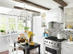 The+black-and-white+handmade+tile+backsplash+in+this+small+kitchen+makes+a+big+design+statement.+Rather+than+sticking+with+a+smaller+pattern,+homeowners Kim+Cornelison+and Alfie+Ferreyra+went+bold+and+chose+the+large-scale+graphic+that+resembles+wallpaper+but+the+cement+tiles+provide+a+slick+surface+that+wipes+clean.+Browse+more+pics+of+this+kitchen+that+was+featured+in+HGTV+Magazine.+