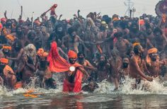 Naga sadhus run in to bathe in the waters of the holy Ganges river during the auspicious bathing day of Makar Sankranti of the Maha Kumbh Mela in Allahabad, on January 14, 2013. (Daniel Berehulak/Getty Images)