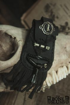 This beautiful medicine pouch is composed of many darker elements. The scrap leather is a nice dark, warm grey, handsewn with artificial black sinew, and black hemp cord. It is hand distressed, and is complimented by its silver cameo, in which lies a single phalanges. SO COOL