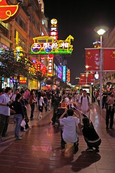 Mom and dad take a picture of their baby with the neon lights of Nanjing Road as a backdrop.
