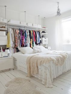 Closet hanging behind the bed gives the room a pop of colour. Love the layering of delicate lace pattern sheets and off white throw. Also floating hangers and white hardwood floor. Everythingggg