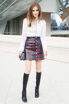 Chiara Ferrgani wears a lace high-neck top, Louis Vuitton skirt, and knee-high boots