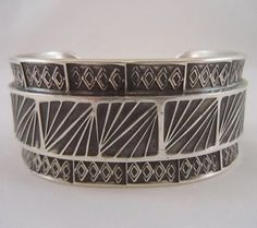 """Description Sterling Bracelet By Barry Petri Heavy – Wide – Beautiful Center Band Overlay:""""Feathered Squares"""" Base:Band overlay is set between bands of Diamond within Diamond Stamps. Inside of Bracelet:Square Spirals Total Number of Stamps Used:5 Very Unique….Original Stampwork This is a wonderful bracelet with a well skilled stamped silver overlay featuring a thorough over and …"""