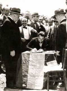 Rodolfo Llopis, sentado, firma por la primera piedra de una escuela junto a Azaña.