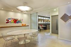 Sala de jantar com mesa Saarinen oval + cadeiras Bertóia + aparador de madeira Canela + luminária La Lampe + quadro colorido David Gerstein. Observem que a cozinha é integrada mas que pode ser isolada com as portas de correr de vidro argentato. Projeto Mônica Drucker, via Uol Casa.