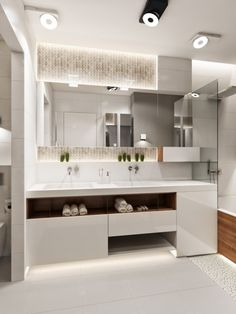 Clean white countertops and plenty of mirrors, with tucked away storage under the his and hers sinks, are useful in keeping the bath clean but never cramped.