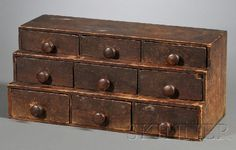 Pine Nine-drawer Stepped Spice Box, New England, early 19th century, the surface with worn brown paint, (wear, stains), ht. 8, wd. 8, lg. 18 in.