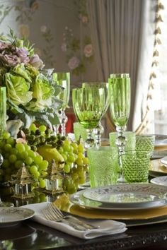 Lovely green glassware and centerpiece of fruit and decorative kale set an elegant table for a dinner party!