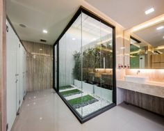 A neat, simply zen internal courtyard brings the green outdoors into a screened-off, windowless bathroom area. The indoor garden provides an...