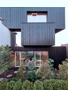 the extension consists of three darkly-clad boxes arranged with 90 degrees shifts to form the overhangs and outdoor terraces.