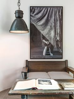 Room with vintage light fixture, white walls, black and white artwork, vintage wooden coffee table, and a wood couch with striped cushions
