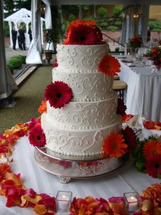 An ivory cake with buttercream swirls and assorted gerbera daisies will make a lovely addition to your wedding reception