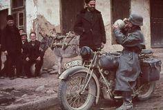 Немецкий мотоциклист утоляет жажду в болгарской деревне, 1940 г.