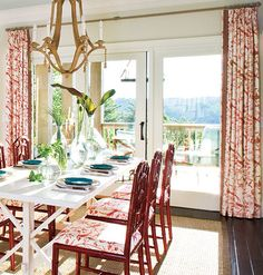 A bold, floral fabric is used on both the curtains and the chairs in this elegant dining room. To elongate the room, a red trim is added to the inside edges of each panel, and the curtains are hung just below the crown molding rather than right over the door frame.