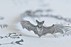 "The Bat Bracelet  Antique Sterling Silver by blackpersimmons, 22.00 A turn of the century tooled, brass stamped bat, has been given a rich antique finish to highlight the detailing. This bat measures 4~3/4"" (120mm) long by 5/8"" (16mm) wide. Made in the USA. There's a gunmetal wing charm at the end!  Gunmetal chain and findings."