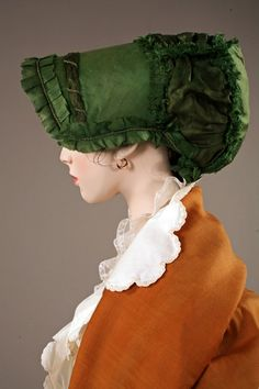 Green silk taffeta bonnet with satin and cord trim, and peach silk lining, French, c. 1808. From the Lancaster-Barreto collection.