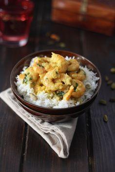 Curry de crevettes  - 400 g de crevettes décortiquées  - 1 oignon haché  - 1 gousse d'ail hachée  - 20 cl de lait de coco  - 1 cube d'or Maggi  - 1 cuillère à soupe de curry en poudre  - 1 cuillère à café de curcuma  - 2 cuillères à soupe de coriandre hachée  - 30 g de beurre  - Sel et poivre
