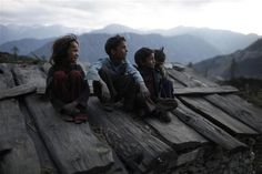 Children watch the approach of a storm on the roof of their home in the remote Mugu District of Nepal.     © UNICEF/Brian Sokol   -  To learn more: http://www.unicef.org/photography