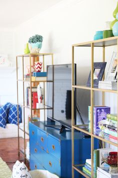 Campaign dresser as TV stand. I love campaign-style furniture reimagined in bright colors and those twin brass etergees aren't too shabby either!