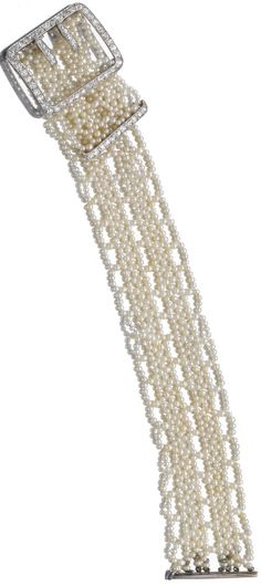 SEED PEARL AND DIAMOND BRACELET, CARTIER The woven band of seed pearls to a buckle set with single- cut diamonds, mounted in platinum, length approximately 170mm, signed Cartier and numbered, French assay and partial maker's marks.