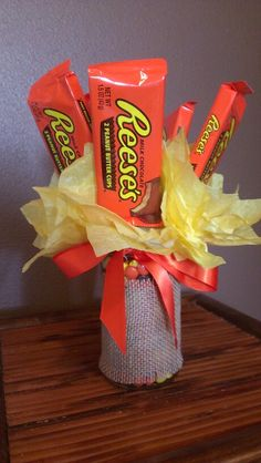 Reese's Candy Bouquet Reese's have a stick taped to the back that are pushed through tissue paper and put in a jar filled with Reese's Pieces. The jar is decorated with burlap and a ribbon.
