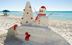 Merry Christmas on the beach. Sand sculpture of snowman, tree and surfboard.
