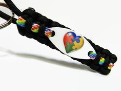 "Show your support with this Autism puzzle heart key chain! The key chain length is about 4.5"", made with black paracord with a tie dye accent in the center!"