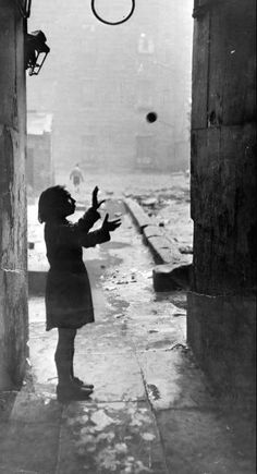 Bert Hardy - 1st January 1948: Sheltering from the rain, a solitary child plays catch in an alley in the Gorbals, one of the poorest areas of Glasgow, Scotland. °