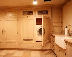 Amazing laundry room with cabinetry to hide washers and dryers and large farm sink.