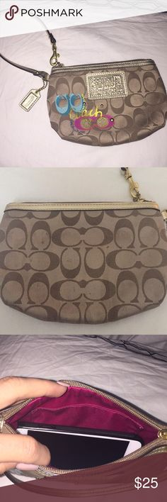 Coach wristlet Perfect little wristlet . Fits all iPhone sizes including iPhone plus. Brown with gold details. Keychain included. Hot pink material inside. Has been used . Has a few small stains if you examine closely. Coach Bags Clutches & Wristlets