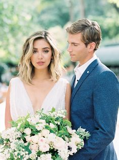 Beautiful wedding portrait. Alexandra Grecco dress. Blue suit. White and blush bouquet with greenery and anemone.