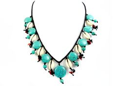 Beautiful handmade statement collier necklace in thai micro macrame style. The collier is richly decorated with turquoise discs and natural cowry shells, elegantly surrounded by turquoise pearls, red coral- and black onyx chips.
