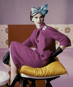 A model wears a fuscia dress suit and hat with bow detail by Emme, 1961.