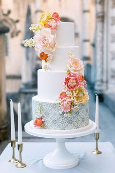 "From the editorial ""Dreaming of a Wedding Destination That Feels Like a Real-Life Fairytale? Look No Further."" This gorgeous four-tier cake by Julie Deffence was decorated with sugar flowers matching the day's color palette and handcrafted wafer paper with the same typical Portuguese tile pattern. Photography: @malvina_frolova #weddingcake #grandweddingcake #flowerweddingcake #floralweddingcake"