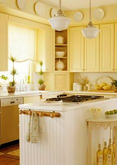 simple cottage style kitchen. Love the yellow, the school house lights and the beadboard