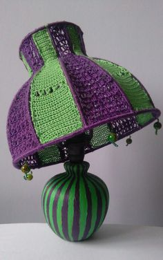 The Mad Hatter is a small upcycled tabletop or bedside lamp which will enliven any ambience with its bold colours and quirky shapes.  It is a decorative piece in itself, whether lit or unlit and truly one of a kind. The lampshade is made of hand- crocheted mercerised cotton and has decorative green bead pendants attached at the bottom. The lamp has a ceramic, bulb-shaped, striped stand.  For more info or to buy, click the link below Crochet Lamp, Hand Crochet, Vintage Lamps, Vintage Table, Bohemian Lamp, Bold Colors, Colours, Home Decor Quotes, Quirky Home Decor