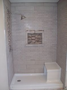 Had to convert a tub into a shower for handicapped access. Kohler shower base with built in bench. Lowes tile in 4 different sizes (floor not pictured) Leonia Silver. Mosaic is Lowes Java glass and stone strips.
