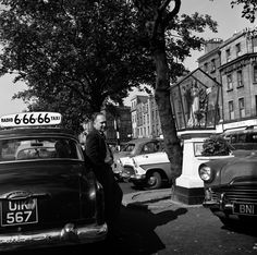 Ireland Taxi driver waiting for a fare (and chatting to another driver leaning on his car?) at the rank in Dublin's O'Connell Street beside the Sacred Heart Shrine. Photographer: Elinor Wiltshire Date: Summer 1964 Dublin Street, Dublin City, Old Pictures, Old Photos, Irish Catholic, Michael Collins, Somewhere In Time, Ireland Homes, Al Capone