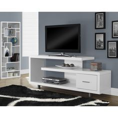 House your television and gaming units in beautiful style with this modern TV console finished in white for a seamless blend with your decor. This piece features multiple levels for assorted devices and a pull-out drawer for your accessories.