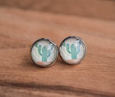 This pair of desert cactus earrings is made using high quality prints of a potted cactus sealed behind magnifying glass domes. They are attached to 14 mm silver earring studs with backings. Add a touc