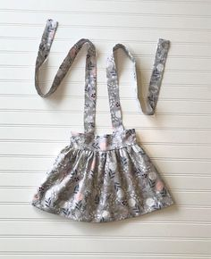 This adorable handmade suspender skirt is made of a soft cotton floral fabric. It is fully lined in a soft white cotton fabric.