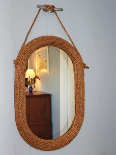Beach House Rope-Covered Mirror - and it's hung off of one of those things on a boat that you tie the rope to (forget what they're called).  I could do this for the bathroom.
